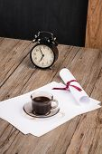 stock photo of private investigator  - Old clock hat coffee and paper sheets on old Wooden table - JPG