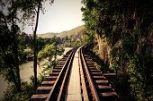 image of train track  - Train track with river and mountain view railway in Thailand - JPG
