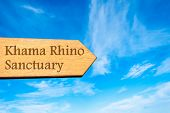 picture of rhino  - Wooden arrow sign pointing destination Khama Rhino Sanctuary Botswana against clear blue sky with copy space available - JPG