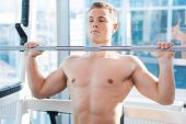 pic of work bench  - Concentrated young muscular man working out on bench press - JPG