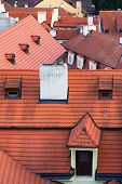 stock photo of red roof  - Red tiled roofs of houses with pipes of different windows in Prague - JPG