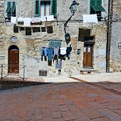 pic of downspouts  - Drying Clothes on the Facade of Italian House Vintage Style Toned Picture - JPG