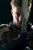 picture of sword  - Ancient knight in metal armor with sword on gray background - JPG