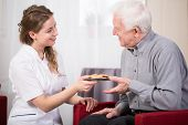 foto of guardian  - Pretty smiling female guardian serving cookies to older man