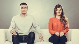 stock photo of shy woman  - Shy woman and man. Guy sitting near attractive young woman on sofa and making hand gesture walking with finger to girl