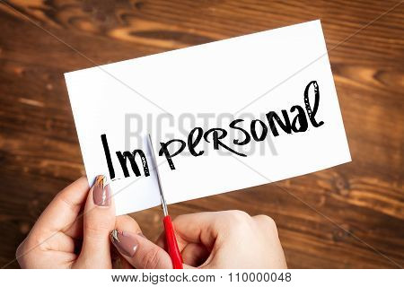 Woman hands cutting card with the word impersonal