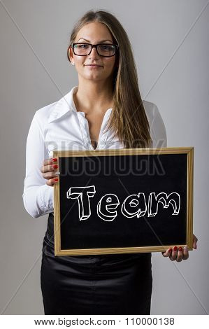 Team - Young Businesswoman Holding Chalkboard With Text