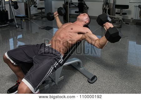 Muscular Man Doing Exercise For Chest With Dumbbells