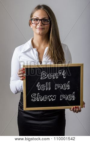 Don't Tell Me! Show Me! - Young Businesswoman Holding Chalkboard With Text
