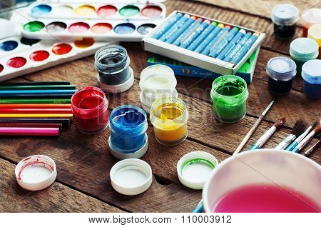 Art of Painting. Paint buckets on wood background. Different paint colors painting on wooden backgro