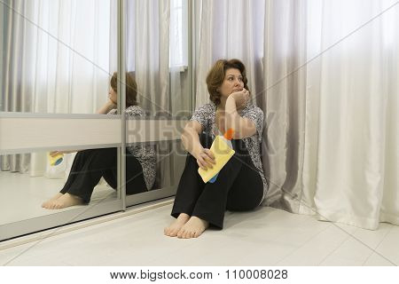 Tired of cleaning housewife sitting on  floor