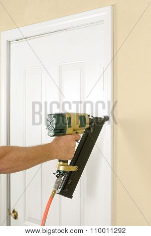 Carpenter using an angle nail gun to finish door trim