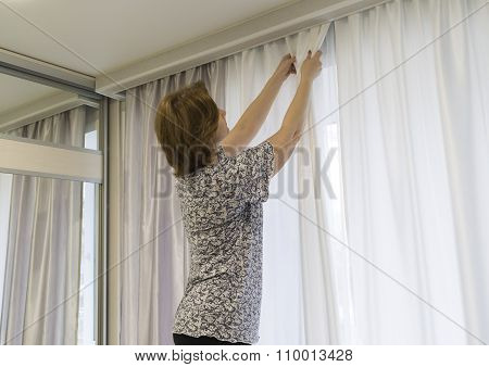 Woman hanging up her curtains at  window