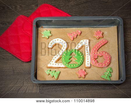 Home-made gingerbread cookies in shape of 2016 New Year digits on baking tray