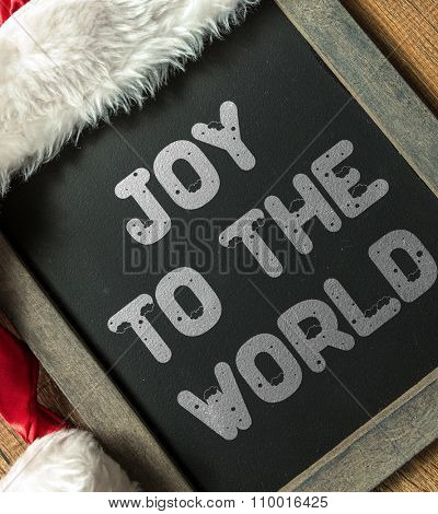 Joy to the World written on blackboard with santa hat