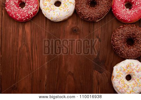 colorful donuts lying on brown wooden table like a frame with empty copyspace