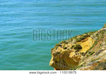 Man fishing from the spectacular rock formations on t