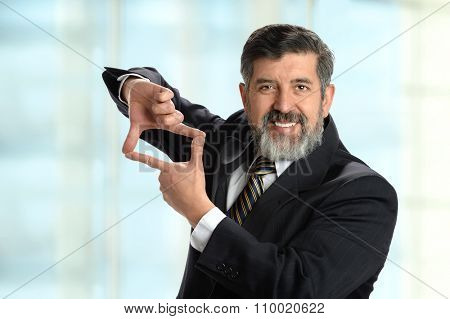 Portrait of Hispanic businessman creating frame with hands inside office environment
