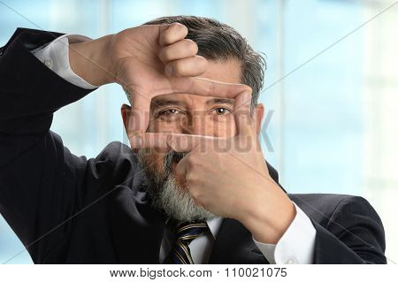 Portrait of Hispanic businessman making frame with hands inside office environment