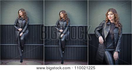 Charming young brunette woman in black leather outfit, coat and trousers, on dark gray wall
