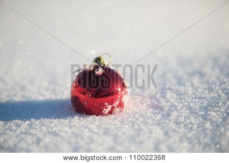 christmas red balls decoration in fresh snow background on beautiful sunny winter day