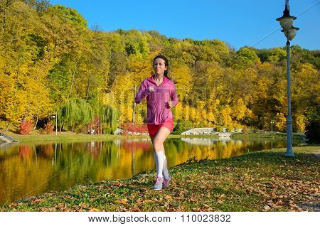 Woman running in autumn park, beautiful girl runner jogging outdoors, training for marathon