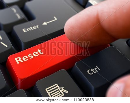 Finger Presses Red Keyboard Button Reset.