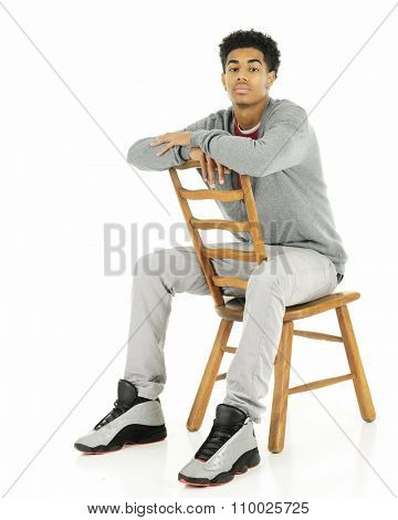 Full length veiw of a tall, older teen serious and sitting backwards on an old ladder back chair.  On a white background.