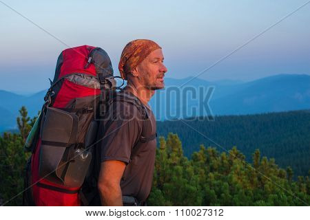 Hiker With Backpack Looks Into The Distance