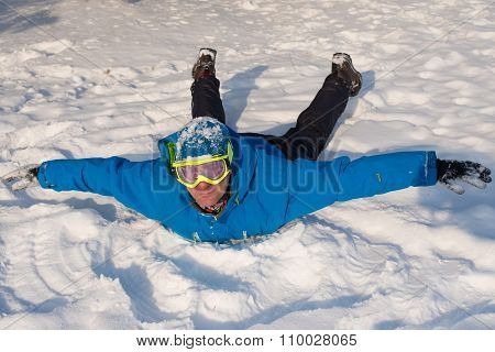 Man With Ski Goggles Is Having Fun At Winter. Smiling Man Is Lying On The Snow