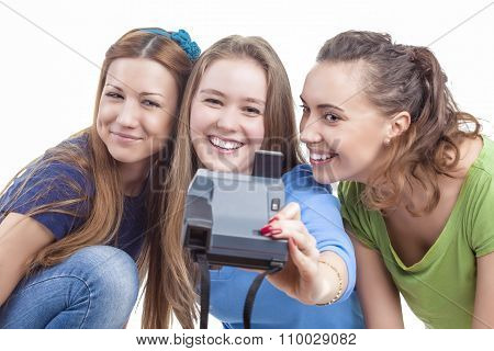 Three Young Happy Caucasian Females With Photocamera Taking Selfie Photographs. Isolated Over White
