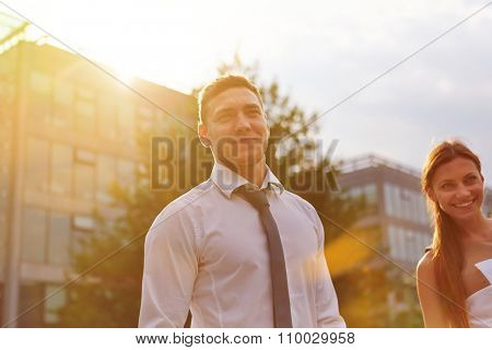 Young business people smiling together in back light in summer