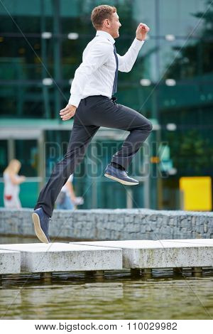 Happy businessman jumping for motivation over abstacle