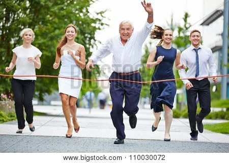 Senior manager cheering when taking leadership in a business race to the finish line