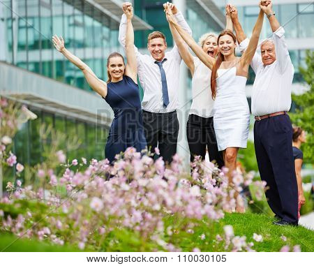 Successful business team cheering together with their arms up in the air