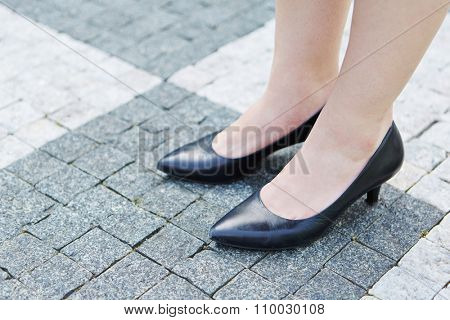 Woman with feet in shoes standing on paving stones