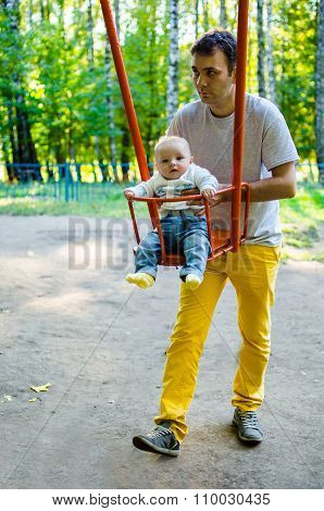 Father And Son On A Swing In A Park