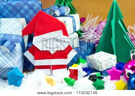 Santa Claus And Gift Box With Small Star Paper On The Snow Field.