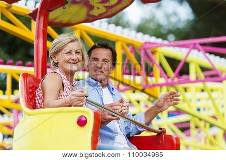 Senior Couple In Amusement Park