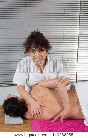 Female Osteopath Treating Female Patient For Hip Problem