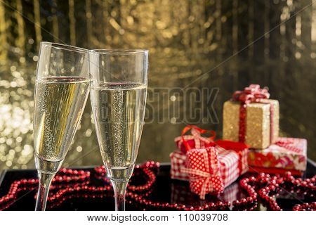 Glasses Of Champagne With Gift On Background