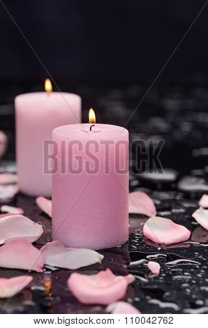 Set of rose petals with two candle and therapy stones-wet background