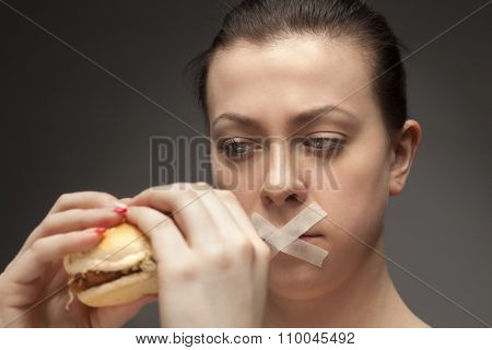 Diet concept: woman holding burger with mouth sealed