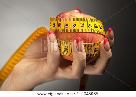 Diet concept: apple with measure tape in woman hand