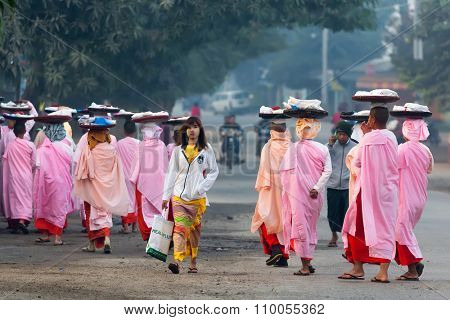 BAGAN, MYANMAR, JANUARY 25, 2015 : A row of Buddhist nuns carrying plates on head for morning alms is walking in the streets of Bagan in Myanmar (Burma)
