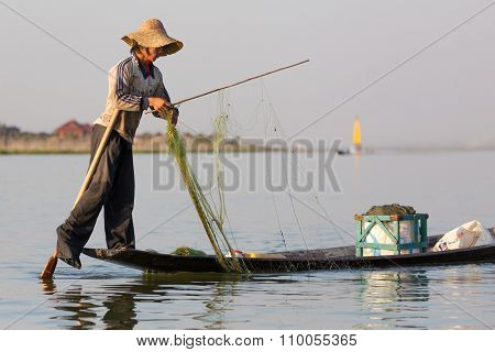 INLE LAKE, MYANMAR, JANUARY 26, 2015 : A fisherman showing the special technical rowing of the Burmese tradition using his leg to handling the paddle in the Inle lake, Myanmar (Burma).