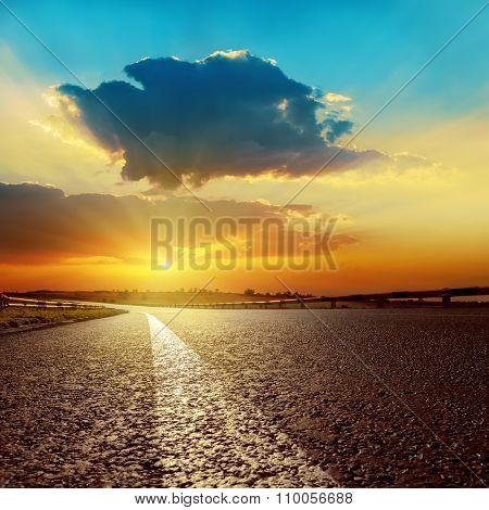 dark clouds over asphalt road on sunset