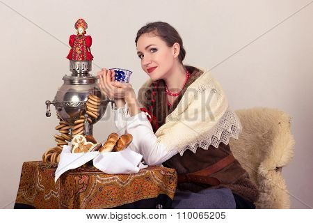 Smiling dreaming rural woman with bagels and cup of tee in shawl in New Year's Eve.