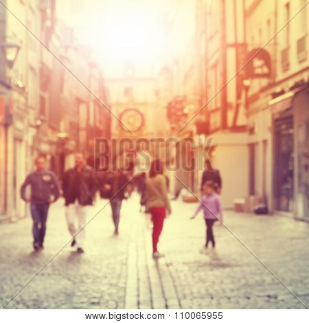Blurred image of people walking on the street at sunset.