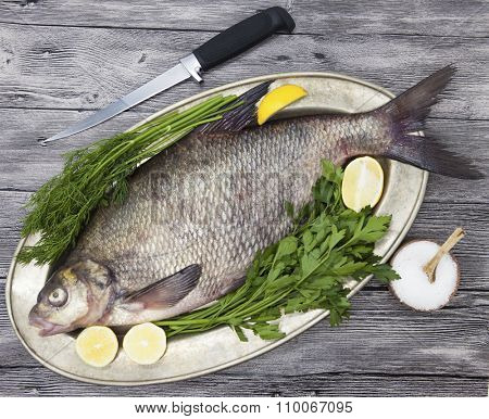 A large live bream river fish  fish lying on a on on an iron tray with a knife and slices of lemon and with salt dill.